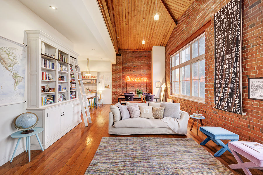 Interior of a warehouse conversion living room with high ceilings, timber floorboards and exposed brick walls